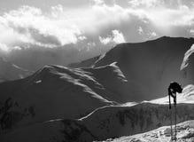 Montañas de la luz del sol de la tarde y equipo blancos y negros del esquí Foto de archivo libre de regalías