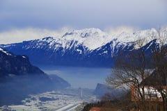 Montañas de la nieve ANG de las nubes bajas el pueblo debajo de las nubes Foto de archivo