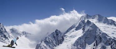 Montañas de la nieve del panorama con el snowboarder Fotos de archivo