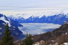 Montañas de la nieve Nubes bajas Imagenes de archivo