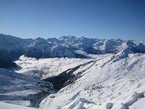 Montañas de la nieve sobre las nubes Fotos de archivo libres de regalías