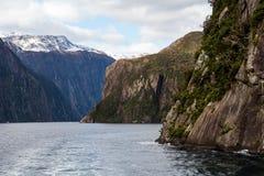 Montañas de Milford Sound en agua imagenes de archivo