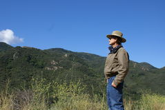 Montañas de mirada solas del hombre mayor en Fotografía de archivo