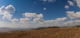 Montañas debajo del cielo azul con las nubes Foto de archivo libre de regalías