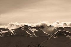 Montañas del invierno de la tarde de la sepia y nubes de la luz del sol Foto de archivo libre de regalías