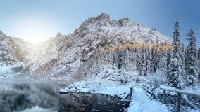 Montañas del invierno del paisaje Rocas nevosas que sorprenden y lago helado Hermosa vista en la alta montaña cubierta por la nie imagenes de archivo