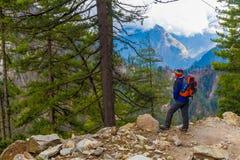 Montañas del rastro de la mochila de la chaqueta del hombre joven del deporte que llevan El senderismo de la montaña oscila el fo Foto de archivo libre de regalías