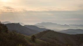 Montañas en el amanecer iluminado por los rayos del sol a través de las nubes almacen de metraje de vídeo
