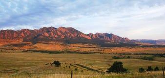 Montañas en el borde de la pradera en la salida del sol fotos de archivo