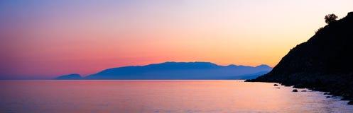 Montañas en la playa en la puesta del sol Foto de archivo