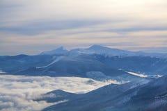 Montañas en las nubes en el invierno Imágenes de archivo libres de regalías