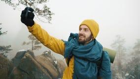 Montañas hermosas en invierno El hombre con la barba, ropa amarilla del invierno que lleva toma el selfie contra la perspectiva d metrajes