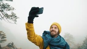 Montañas hermosas en invierno El hombre con la barba, ropa amarilla del invierno que lleva toma el selfie contra la perspectiva d almacen de video