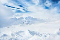 Montañas nevadas del invierno y cielo azul con las nubes blancas Fotografía de archivo libre de regalías