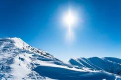 Montañas Nevado con el sol Imágenes de archivo libres de regalías
