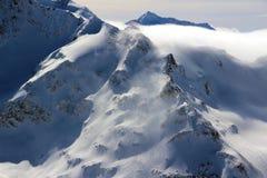 Montañas Nevado en el cielo azul el Cáucaso Elbrus de las nubes Imagen de archivo