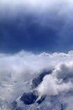 Montañas Nevado en nubes y cielo de la luz del sol Foto de archivo libre de regalías