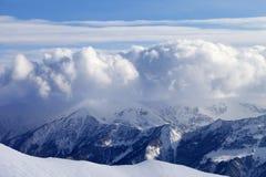 Montañas Nevado en nubes y cuesta fuera de pista Foto de archivo libre de regalías
