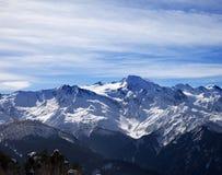 Montañas nevosas de la luz del sol y cielo nublado Imagen de archivo libre de regalías
