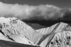 Montañas nevosas soleadas blancos y negros por la tarde Fotos de archivo