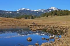 Montañas reflejadas en el agua Foto de archivo libre de regalías