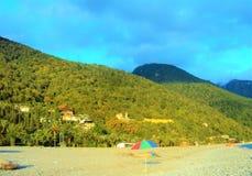 Montañas rizadas verdes contra el cielo azul y la playa con los parasoles de playa Foto de archivo