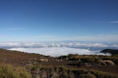 Montañas sobre las nubes y el cielo azul Fotos de archivo libres de regalías