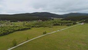 Montañas verdes bajas y el camino en la base de las montañas almacen de metraje de vídeo