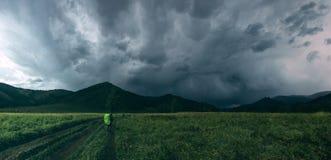 Montañas verdes y nubes oscuras Imagenes de archivo