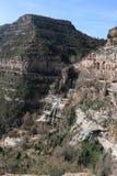 Montañas y cascada sobre rocas acantiladas Imagenes de archivo