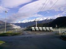 Montañas y coches coronados de nieve foto de archivo