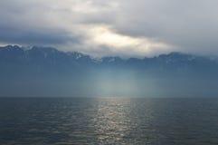 Montañas y lago en tiempo nublado Foto de archivo