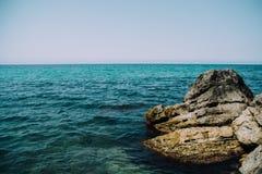 Montañas y mar azul con las rocas Foto de archivo