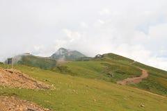 Montañas y prados verdes en las nubes imagen de archivo