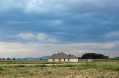 Montañas y una casa con el cielo dramático Foto de archivo