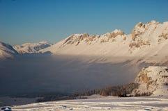 Montañas y valle Coverd Nevado en niebla imagen de archivo