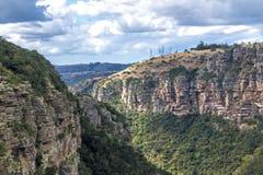 Montañas y valles verdes de la garganta de los árboles contra el cielo nublado imagen de archivo libre de regalías
