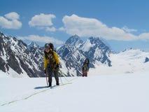 Montañeses en las montañas de la nieve fotografía de archivo