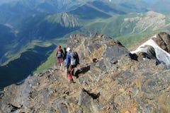 Montañeses en las rocas de la montaña imagenes de archivo
