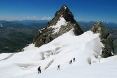 Montañeses en nieve y rocas foto de archivo