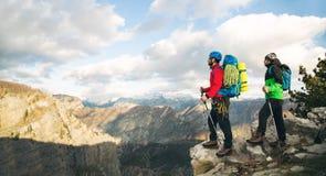Montañeses jovenes que se colocan con la mochila encima de una montaña imagen de archivo libre de regalías