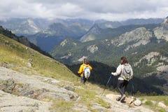 Montañeses que van abajo de las montañas en una excursión Imagen de archivo libre de regalías