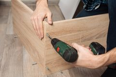 monta? mebli Mężczyzna ręki z śrubokrętem zbierać nowego meble zdjęcia stock
