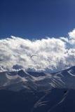 Montaña del invierno por la tarde y la silueta del paracaidista Foto de archivo
