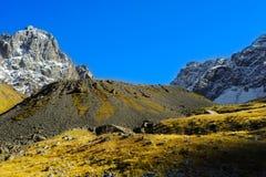 Montañas del Cáucaso, pueblo Juta colina verde, cielo azul, y pico nevoso Chaukhebi en verano Imágenes de archivo libres de regalías