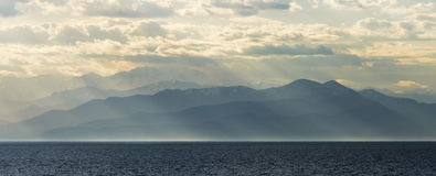 Montañas por el mar en sol Fotos de archivo