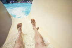 Montada abaixo de uma corrediça em um recurso do waterpark Fotografia de Stock Royalty Free