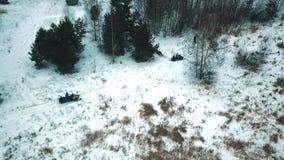 Montada dos jovens carros de neve em um tiro do helicóptero da floresta do inverno video estoque