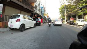 Montada em um velomotor ao longo da terraplenagem asiática de Jomtien tailândia Pattaya filme