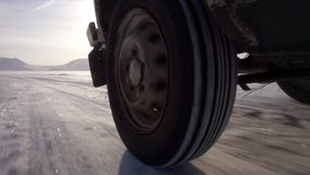Montada no gelo do lago e de muita neve A roda traseira do carro filme